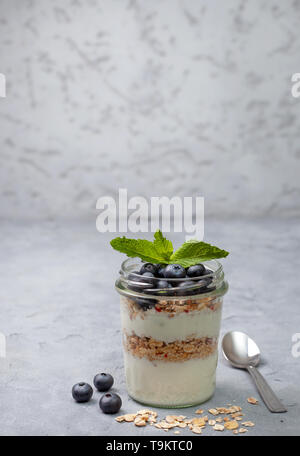 healthy breakfast. yogurt with granola and blueberries in a glass on a gray concrete background - Stock Image