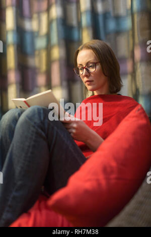 Woman reading book, relaxing - Stock Image