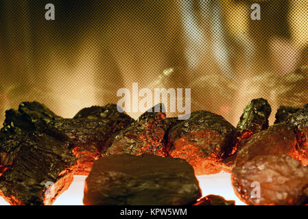 Black artificial black coal and coke burning on a fake fire in a fireplace - Stock Image