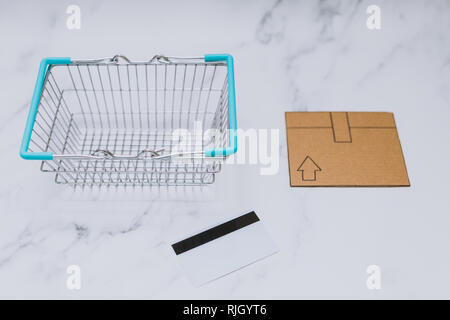 payment card next to empty shopping basket and mini cardboard delivery parcel, concept of shopping online - Stock Image