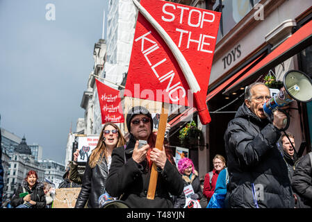 Protesters at a stop trophy hunting and ivory trade protest rally, London, UK. Elephant tusk placard - Stock Image