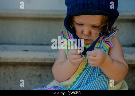 A toddler girl tries to hook her winter hat while standing outside on a warm day. - Stock Image