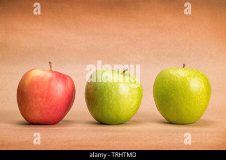 Three apples, two green and one red, on craft paper background with copy space - Stock Image
