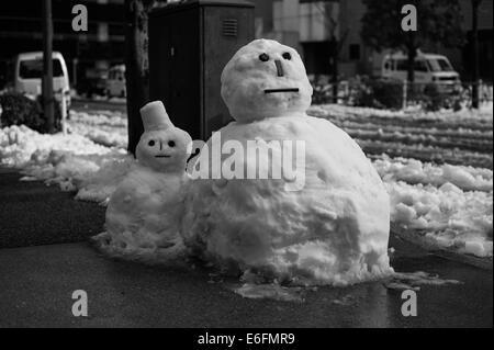 Two snowmen on a side street in Tokyo - Stock Image