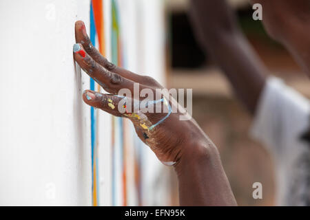 Artist's hands covered in paint whilst doing a mural, Kigali, Rwanda - Stock Image