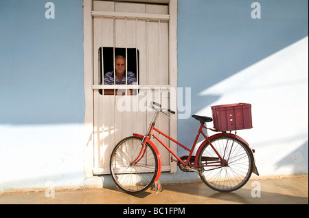Cuban man peering through a hatch in the door way to his home. Bicycle outside. Viñales, Cuba - Stock Image