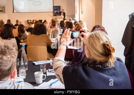 Blonde white middle-aged woman holds up her smartphone to take a photo of a powerpoint presentation at a conference with lots of people in the room - Stock Image