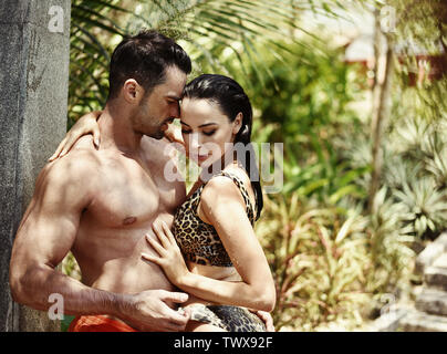 Portrait of a young, romantic couple taking a tropical shower - Stock Image