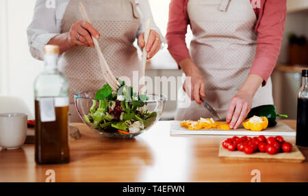 A midsection of unrecognizable women at home, preparing vegetable salad. - Stock Image