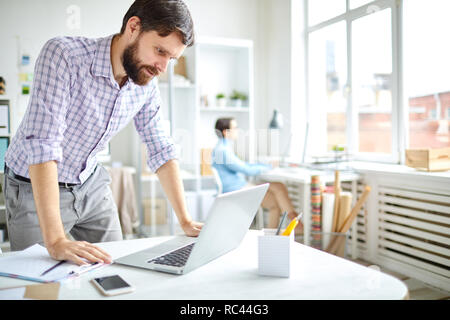 Young bearded office worker bending over desk with laptop and looking through online data or watching business news review - Stock Image