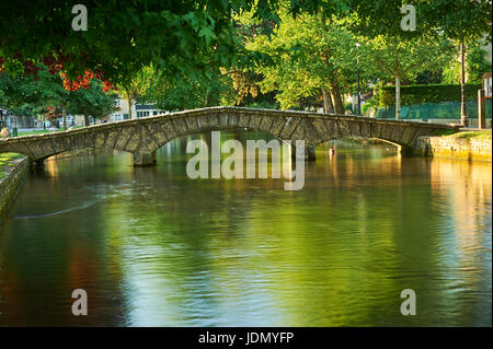 A summer morning and small stone footbridges over the River Windrush in the picturesque Cotswold village of Bourton - Stock Image