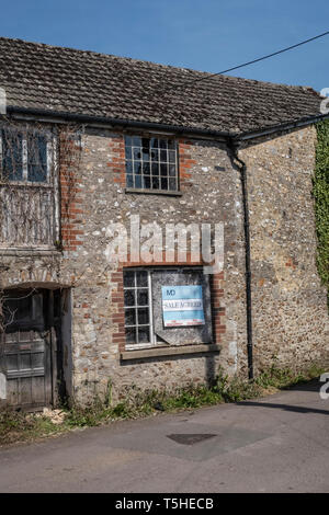 Run down derelict building in Colyton, Devon, UK, with sale agreed sign.Overgrown, with broken windows. - Stock Image
