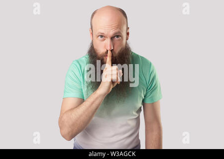 Be quiet. Portrait of serious middle aged bald man with long beard in light green t-shirt standing with finger on lips and showing silence sign. indoo - Stock Image