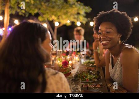 Happy women friends enjoying dinner garden party - Stock Image