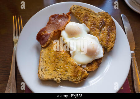 Lunch open sandwich of two poached eggs on  toasted multigrain bread topped with grilled smoked bacon - Stock Image