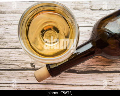 Top view of a glass of dry white wine and a bottle lying on an old wooden background. - Stock Image