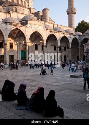 Tourists and worshippers in the courtyard of the Blue Mosque, Sultanahmet, Istanbul, Turkey - Stock Image