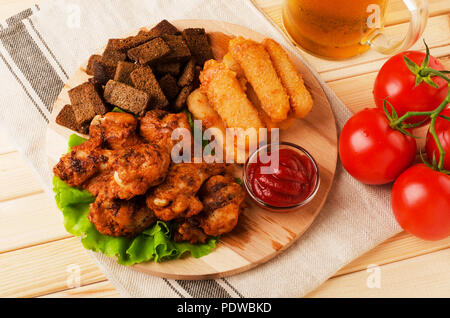 Fried wings, dried bread and cheese sticks with mug beer, served with sauces on a wooden background - Stock Image