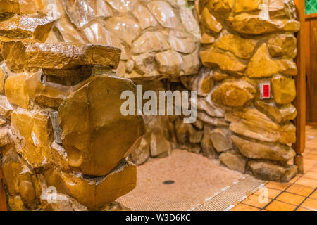 The infamous and kooky waterfall urinal at the Madonna Inn Hotel in San Luis Obispo, California where men can pee into a running waterfall. - Stock Image