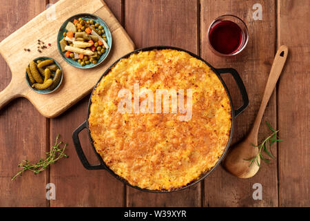 Homemade Shepherd's pie in a cooking pan with pickles and wine, shot from the top on a dark rustic wooden background - Stock Image