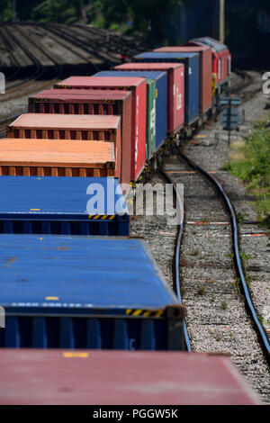 Container railway train travelling  on the main line into Southampton and Southampton Docks carring goods for export and import. - Stock Image