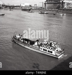 1960s, historical, busy tourist board leaving westminster pier to go down the Thames. The office building of the LLC - and later the GCC - can be seen opposite. - Stock Image