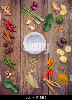 Various of Thai food Cooking ingredients and spice red curry paste ingredient of thai popular food on rustic wooden background. Spices ingredients chi - Stock Image