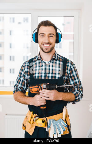 handsome handyman smiling while holding drill in hands - Stock Image
