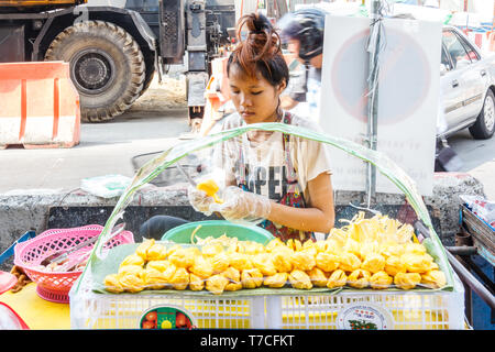 Bangkok, Thailand - 7th March 2017: A girl prepares Durian fruit for sale. Street food stalls are popular with both tourists and locals. - Stock Image