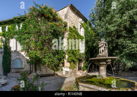Fountain in Saignon, facade with wild wine in autumn, Provence, France - Stock Image