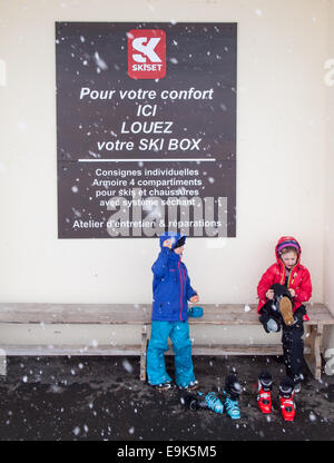 small boy and girl in ski clothing  sitting on a bench putting on ski boots with falling snow and a sign in french - Stock Image