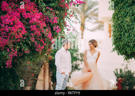 Happy newlyweds walk among blooming trees and flowers during the honeymoon in Egypt. - Stock Image