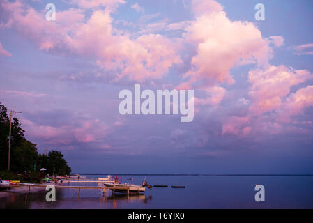View of beautiful sky, a boat and docks on lake at sunset - Stock Image