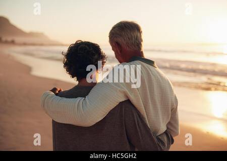 Rear view shot of a senior couple walking on the sea shore. Loving mature couple spending leisurely time on the - Stock Image