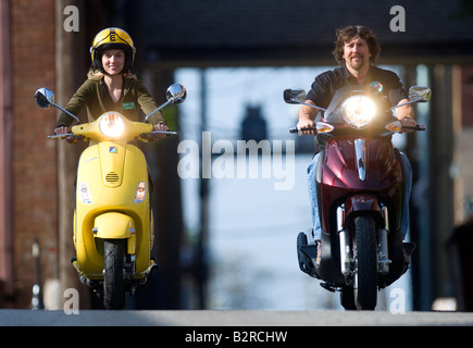 A couple ride their scooters on a street in Rogers, Arkansas, U.S.A. - Stock Image