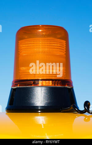 Magnetic Flashing occluding orange beacon on a bright yellow vehicle roof. - Stock Image