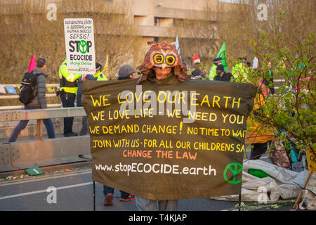 A protestor dressed as an owl holding a banner on Waterloo Bridge for the Extinction Rebellion demonstration - Stock Image