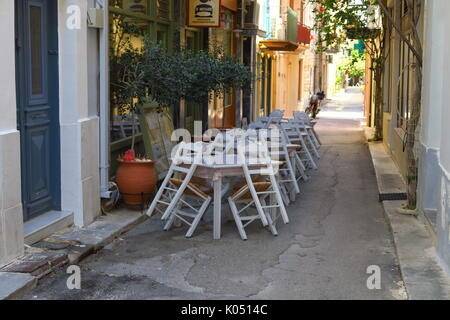Tables and chairs outside a cafe, Nauplion, Greece - Stock Image