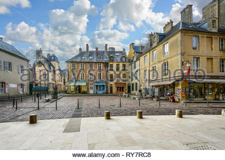 A small square outside the Bayeux Cathedral in Bayeux France with a souvenir shop and stores on a cloudy afternoon in Normandy - Stock Image