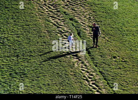 Carefully walking down the steep side of a mound at Northala fields park, Northolt, middlesex - Stock Image