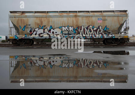 A rain storm in Woodland, CA created a reflection for a box car with interesting graffiti. - Stock Image