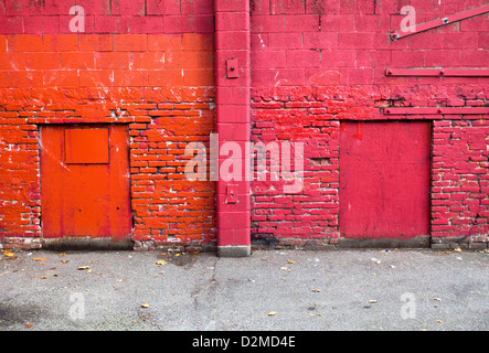 brightly painted rear of buildings from alley - Stock Image