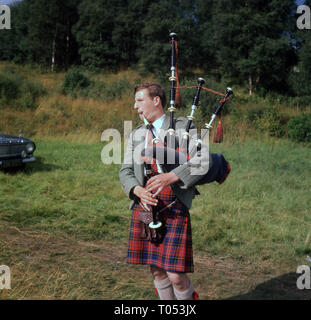 1960s, Scottish piper in tartan kilt playing the bag pipes, Highlands, Scotland, - Stock Image