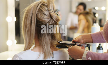 Hairtician twirls curls with flat iron hair. Back view. Hairdressing services. Creation of evening hairstyles fashionable stylish women's hairstyles.  - Stock Image