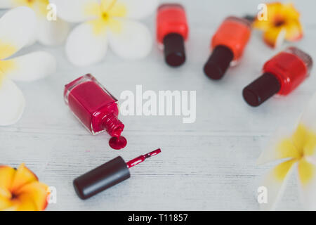 red nail polish bottle and other colors on wooden surface with flowers around it, concept of cosmetics industry and manicure - Stock Image