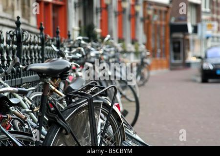 Bike bikes ride riding lock chaining metal fence sidewalk transportation seat Amsterdam Holland rust wheel bikerack - Stock Image