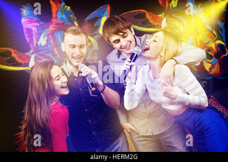 Group happy friends singing karaoke club - Stock Image