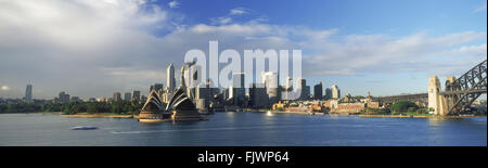Panoramic view of Sydney skyline with Opera House and Harbour Bridge on right with ferryboat taxi crossing - Stock Image