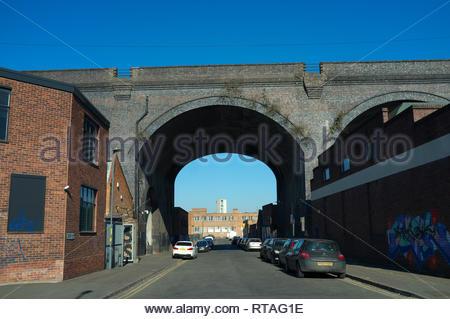 Railway viaduct passes over industrial premises, in Trent Street, central Birmingham, West Midlands, UK. - Stock Image
