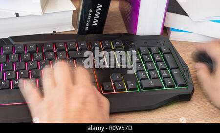 Hand typing on a colored keyboard. Motion blur. Working human hands detail. Computer mouse. Books close-up. Office wood table. A lettering secure www. - Stock Image